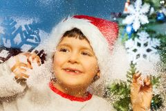 Muchacho detrás adornado para la ventana de la Navidad Imagenes de archivo
