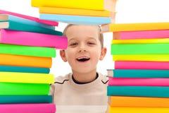 Muchacho detrás de la pila de libros Fotografía de archivo libre de regalías