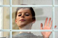 Muchacho detrás de la ventana Imagen de archivo libre de regalías