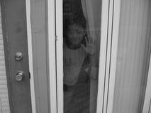 Muchacho detrás de una ventana Imagen de archivo libre de regalías