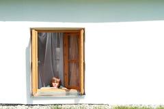 Muchacho detrás en la ventana Fotografía de archivo