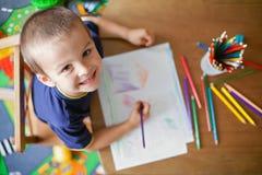 Muchacho, dibujando una imagen para el día de padres Imagen de archivo libre de regalías