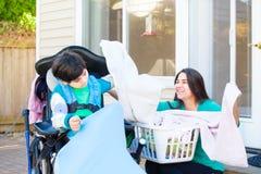 Muchacho discapacitado en la silla de ruedas que ayuda al lavadero adolescente del doblez de la hermana Foto de archivo libre de regalías