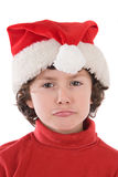 Muchacho divertido con el sombrero rojo de la Navidad que tira de una cara Imagen de archivo