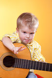 Muchacho divertido con la muestra y la lengüeta de paz de la demostración de la guitarra Fotografía de archivo libre de regalías
