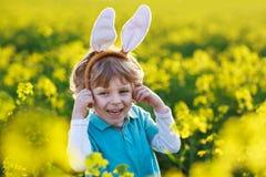 Muchacho divertido de 3 años con los oídos del conejito de pascua, celebrando Pascua Imagen de archivo