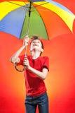 Muchacho divertido de Cheeful en la camiseta roja que sostiene un paraguas multicolor Imagen de archivo