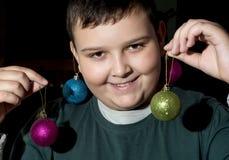 Muchacho divertido de la Navidad con las bolas decorativas Fotos de archivo libres de regalías