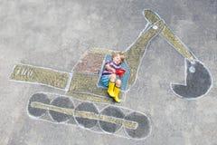 Muchacho divertido del niño con la imagen de la tiza del excavador Foto de archivo