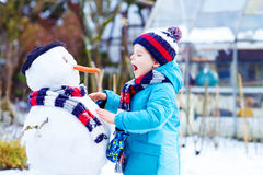 Muchacho divertido del niño en la ropa colorida que hace un muñeco de nieve Imagen de archivo