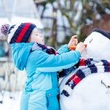 Muchacho divertido del niño en la ropa colorida que hace un muñeco de nieve, al aire libre Imagen de archivo