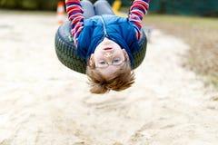 Muchacho divertido del niño que se divierte con el oscilación de cadena en patio al aire libre Imagen de archivo