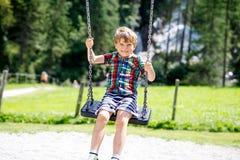 Muchacho divertido del niño que se divierte con el oscilación de cadena en patio al aire libre durante la lluvia Foto de archivo libre de regalías