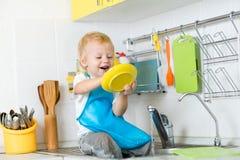 Muchacho divertido del niño que se sienta en la tabla de cocina y el plato que se lava Imagenes de archivo