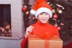 Muchacho divertido del niño que sostiene el regalo de la Navidad en sitio Imagenes de archivo