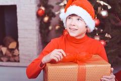 Muchacho divertido del niño que sostiene el regalo de la Navidad en sitio Fotos de archivo libres de regalías