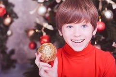 Muchacho divertido del niño que sostiene la bola de la Navidad Fotos de archivo libres de regalías