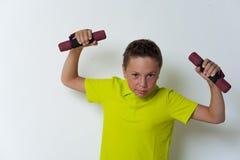 Muchacho divertido del tween que presenta con pesas de gimnasia Imagenes de archivo