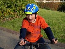 Muchacho divertido en la bici con el casco Imágenes de archivo libres de regalías