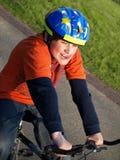 Muchacho divertido en la bici con el casco Foto de archivo libre de regalías