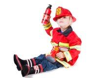 Muchacho divertido en traje del bombero con un casco a salir el lado Imagen de archivo libre de regalías