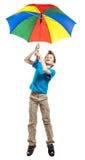 Muchacho divertido hermoso en el vuelo de la camiseta con un paraguas multicolor Imágenes de archivo libres de regalías