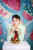 Muchacho divertido que come al hombre dulce de las tortas, hambriento y de caramelo Fotografía de archivo