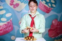 Muchacho divertido que come al hombre dulce de las tortas, hambriento y de caramelo Fotografía de archivo libre de regalías