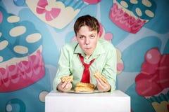 Muchacho divertido que come al hombre dulce de las tortas, hambriento y de caramelo Fotos de archivo