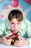 Muchacho divertido que come al hombre dulce de las tortas, hambriento y de caramelo Foto de archivo