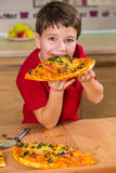 Muchacho divertido que come el pedazo de pizza grande imagen de archivo libre de regalías