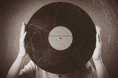 Muchacho divertido que lleva a cabo un viejo expediente retro musical imágenes de archivo libres de regalías