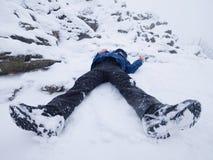 Muchacho divertido que pone en nieve acumulada por la ventisca Embrome el juego del juego en nieve fresca en la colina pedregosa Foto de archivo