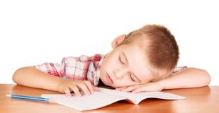 Muchacho dormido en su cuaderno del escritorio aislado en blanco Imágenes de archivo libres de regalías