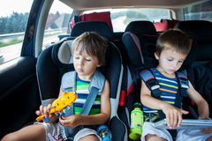 Muchacho dos en los asientos de carro, viajando en coche y jugando con los juguetes y Imagenes de archivo