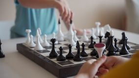 Muchacho dos que juega a ajedrez en sitio ligero Dos hermanos que juegan a ajedrez metrajes