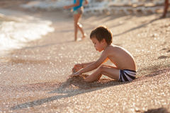 Muchacho dulce del preescolar, playin en la playa con la arena Foto de archivo libre de regalías