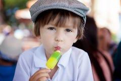 Muchacho dulce lindo, niño, comiendo el helado colorido en el parque Fotografía de archivo