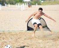 Muchacho durante partido de fútbol de la playa en la arena caliente en verano Imagen de archivo