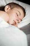 Muchacho durmiente en cama con el espacio de la copia Imágenes de archivo libres de regalías