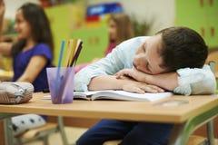 Muchacho durmiente en la sala de clase fotos de archivo