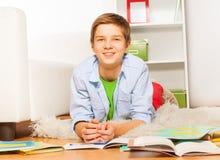 Muchacho elegante adolescente sonriente con los libros en el piso Fotografía de archivo