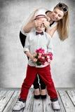 Muchacho elegante con un ramo de rosas que esperan a su mamá para sorprenderla Concepto de la primavera de vacaciones de familia  Imágenes de archivo libres de regalías