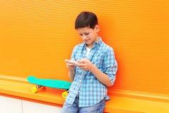 Muchacho elegante del adolescente con el monopatín usando el teléfono en ciudad Imagenes de archivo