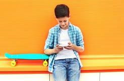 Muchacho elegante del adolescente con el monopatín usando smartphone en ciudad Fotografía de archivo