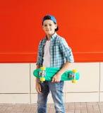 Muchacho elegante del adolescente del retrato con el monopatín en ciudad Fotos de archivo libres de regalías