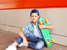 Muchacho elegante del adolescente del retrato con el monopatín en ciudad Imagen de archivo libre de regalías