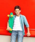 Muchacho elegante del adolescente del retrato que lleva una camisa a cuadros con el monopatín en ciudad Imágenes de archivo libres de regalías