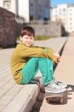 Muchacho elegante del niño que se sienta en el monopatín al aire libre Foto de archivo libre de regalías