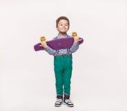 Muchacho elegante del niño que sostiene su monopatín del regalo de cumpleaños fotografía de archivo libre de regalías